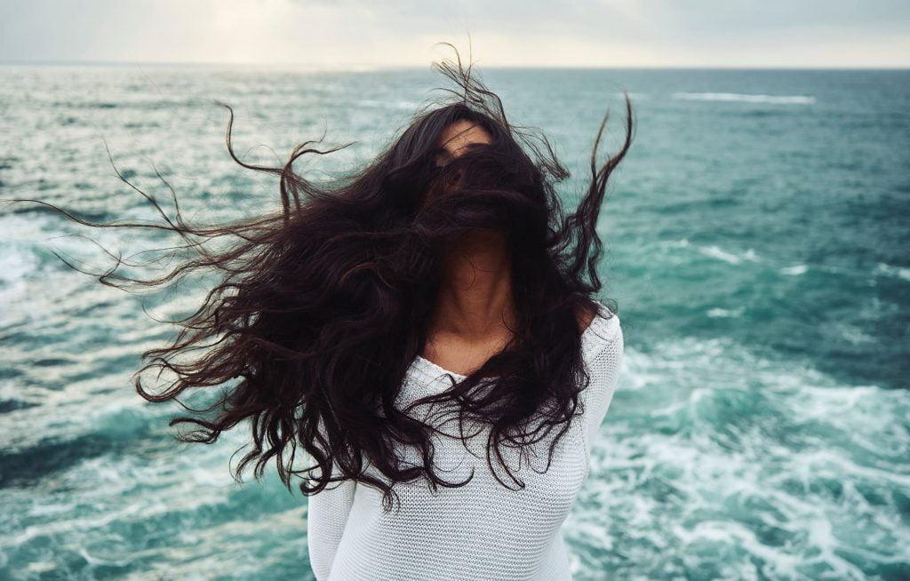Mergina palaidais plaukais, blaškomais vėjo, jūros fone